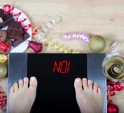 """An image of digital scale with female feet on them and sign """"no!"""" surrounded by christmas decorations and sweets."""
