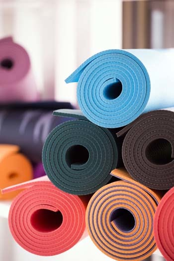 An image of a pile of different color and size yoga mat