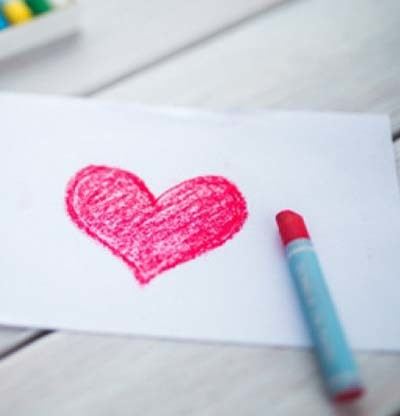 An image of pink heart drawn on paper with a crayon.