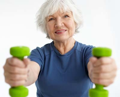 An image of a woman in her sixties gaining strength in gym, training with dumbbells, doing bicep curls