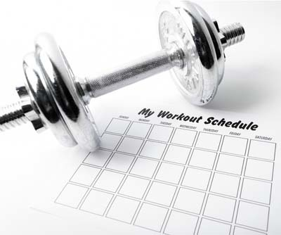An image of workout schedule sheet and dumbbell