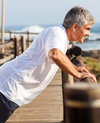 An image of a senior man exercising at the beach in the morning