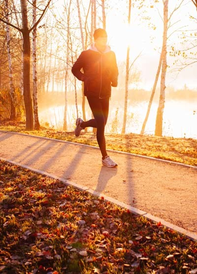 A man running on side of the road with a sunrise.in behind