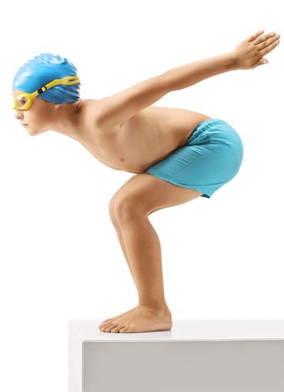 An image of a little boy swimmer ready to dive in water