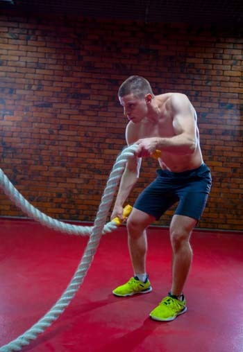 An image of muscular shirtless man in a gym exercises with battle ropes during his fitness workout high-intensity interval training