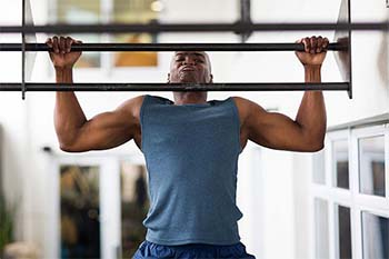 An image of strong guy doing pull-ups on a bar in a gym