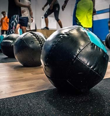 An image of medicine balls lined up in a gym