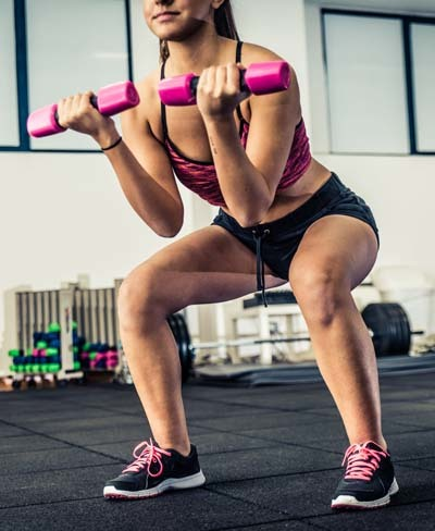 An image of woman doing squats in fitness center
