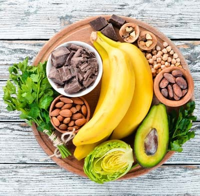 An image of a plate full of Magnesium (MG) Rich Foods: Chocolate, banana, cocoa, nuts, avocados, broccoli, almonds