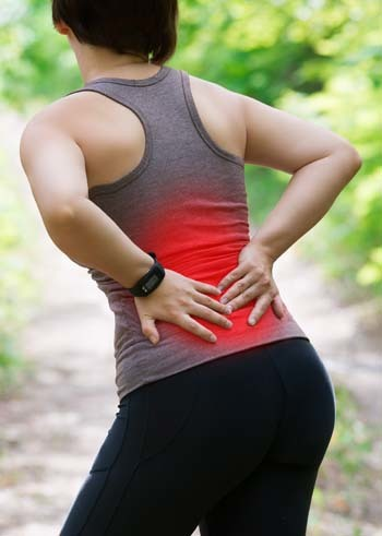 An image of a woman with back pain injury during workout