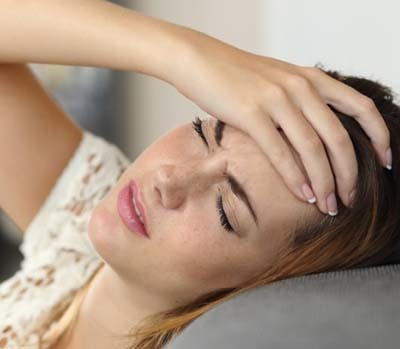 An image of woman suffering from headache.
