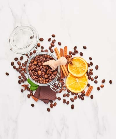 An image of coffee beans with different spices on a white marble top