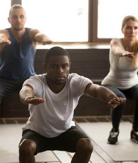 An image of an gym instructor leading a working training squats
