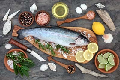An image of Trout Fish on an olive wood board with seasoning