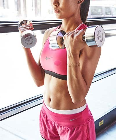 An image of a girl doing workout with dumbbells