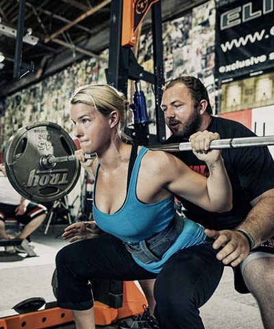 An image of a girl doing weightlifting with trainer