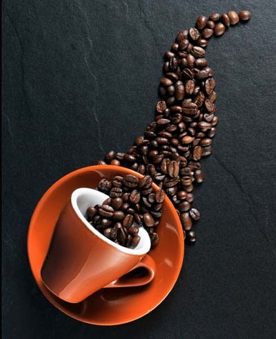 An image of a coffee beans with orange color cup and saucer
