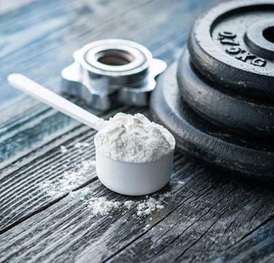 An image of Creatine scoop with dumbbell plates