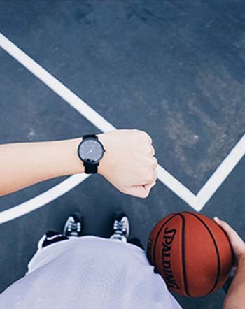 An image of a boy watching time and holding a basketball