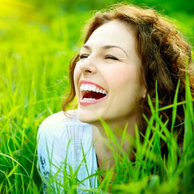 An image of a girl smiling in the garden.